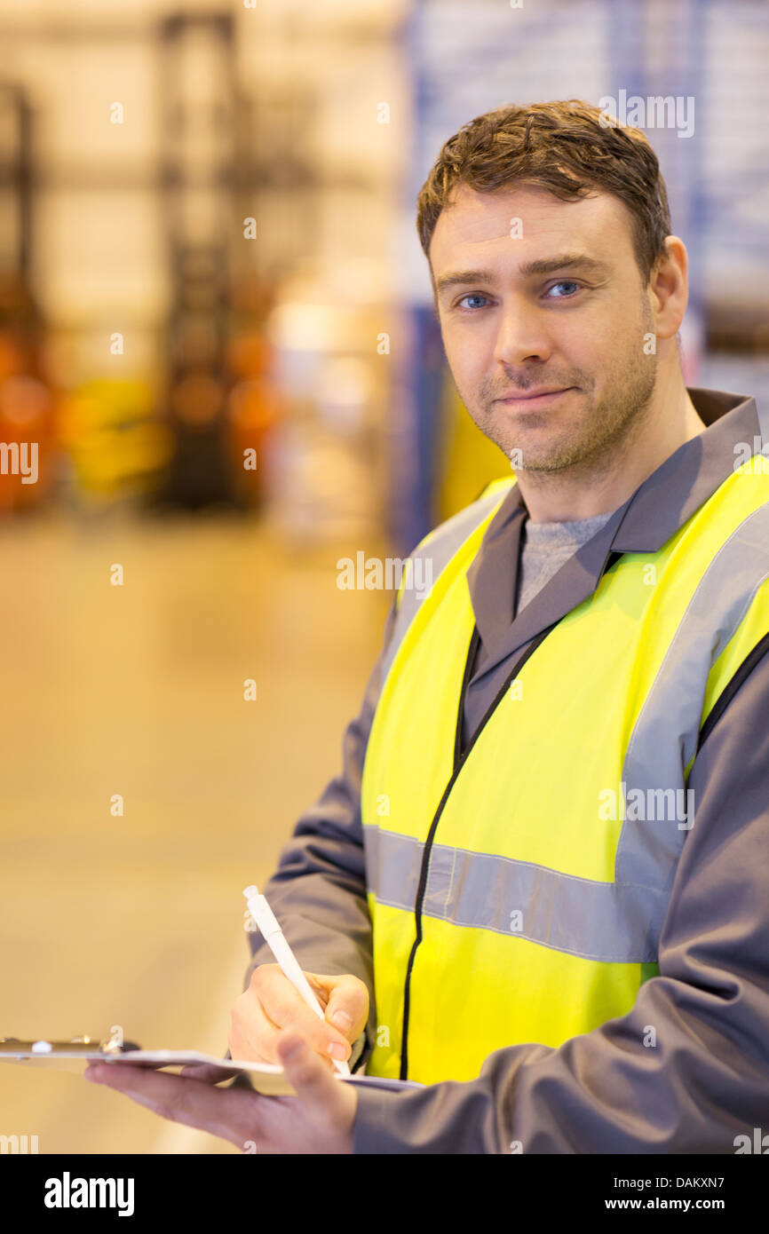Worker using clipboard in warehouse Stock Photo