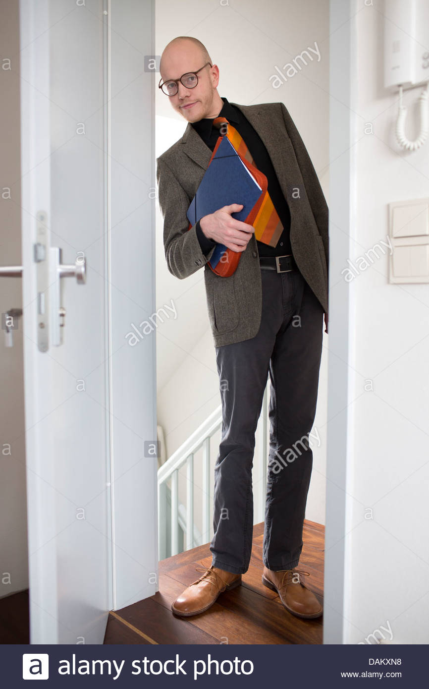 Sales executive standing at the entrance of a house - Stock Image