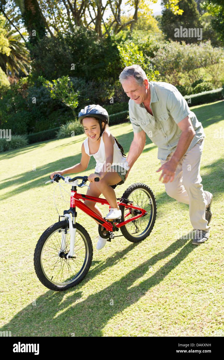 Older man teaching granddaughter to ride bicycle - Stock Image