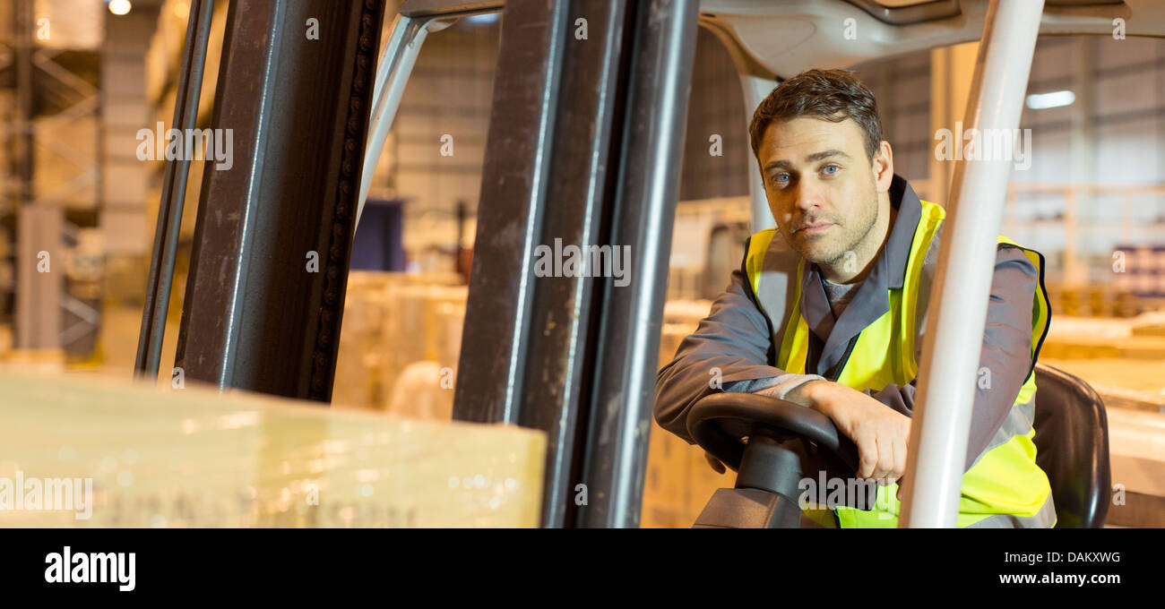 Worker operating machinery in warehouse - Stock Image