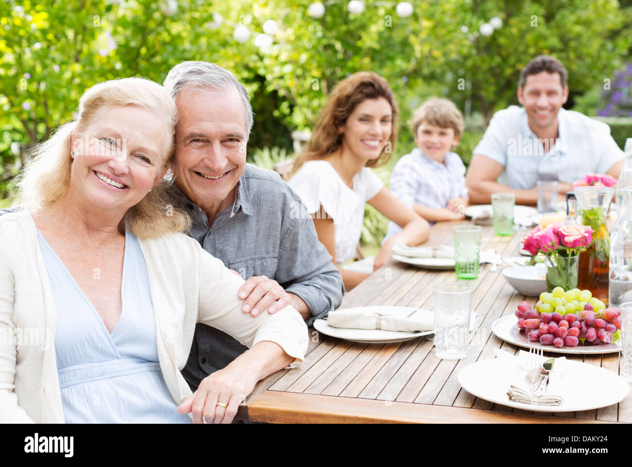Family smiling at table outdoors - Stock Image