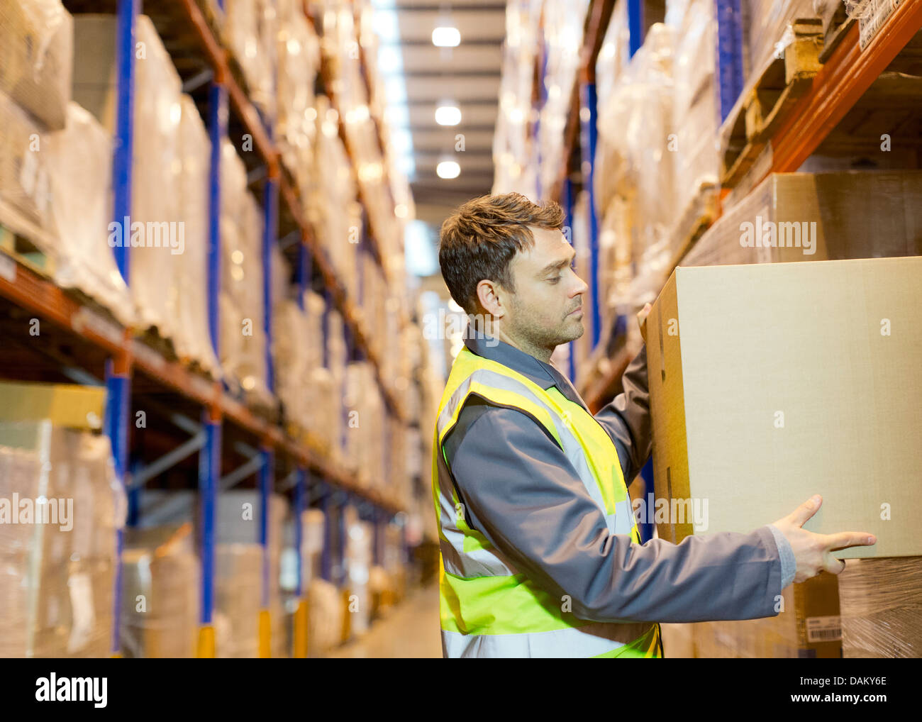 Worker stacking boxes in warehouse - Stock Image