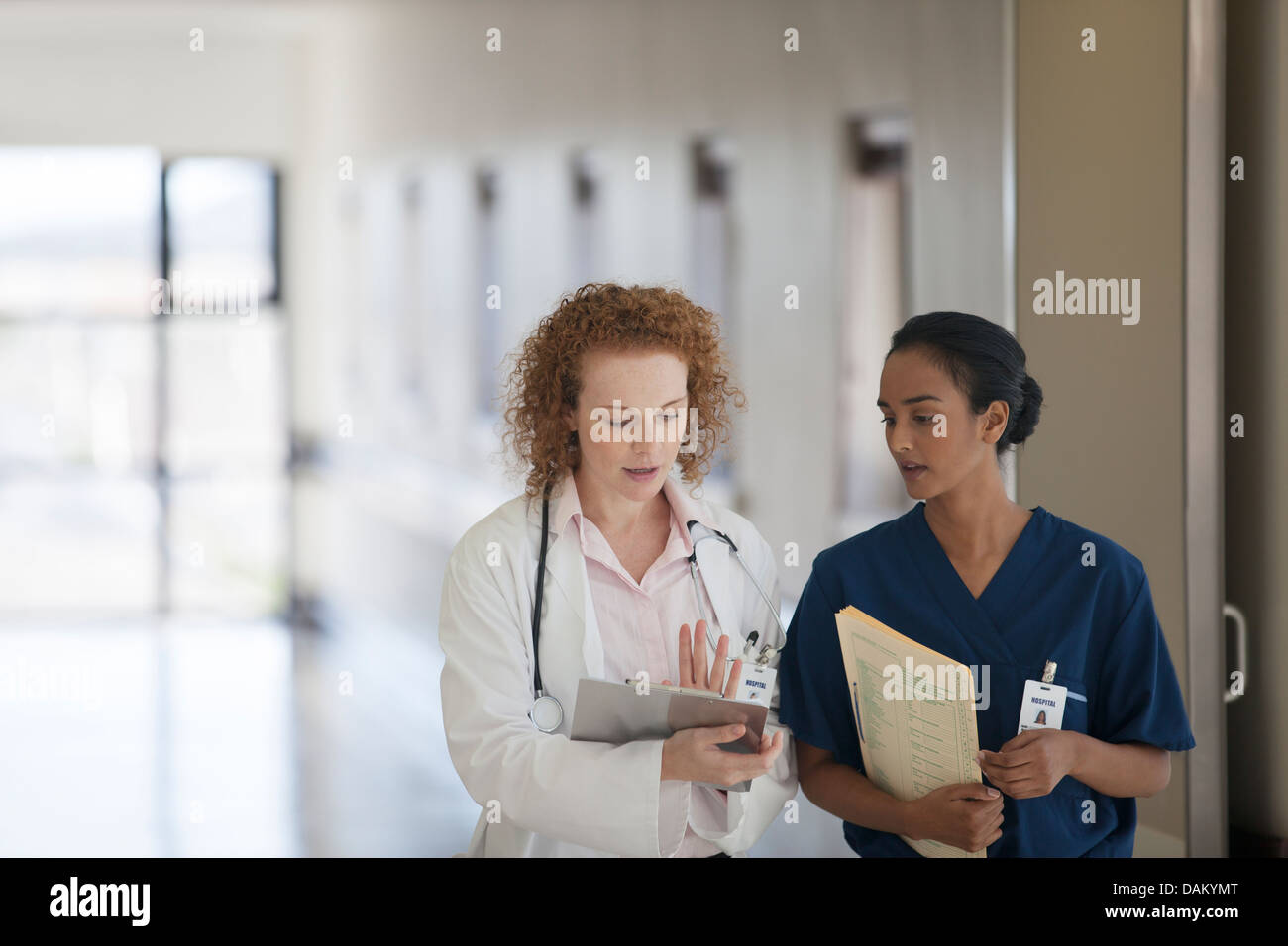 Doctor and nurse talking in hospital hallway - Stock Image