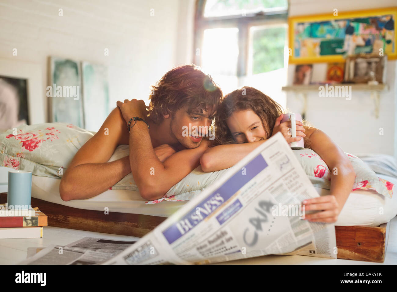 Couple reading newspaper together in bed - Stock Image