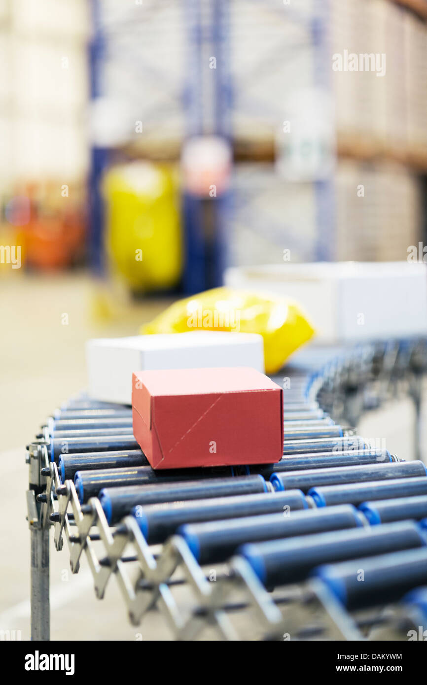 Packages on conveyor belt in warehouse - Stock Image