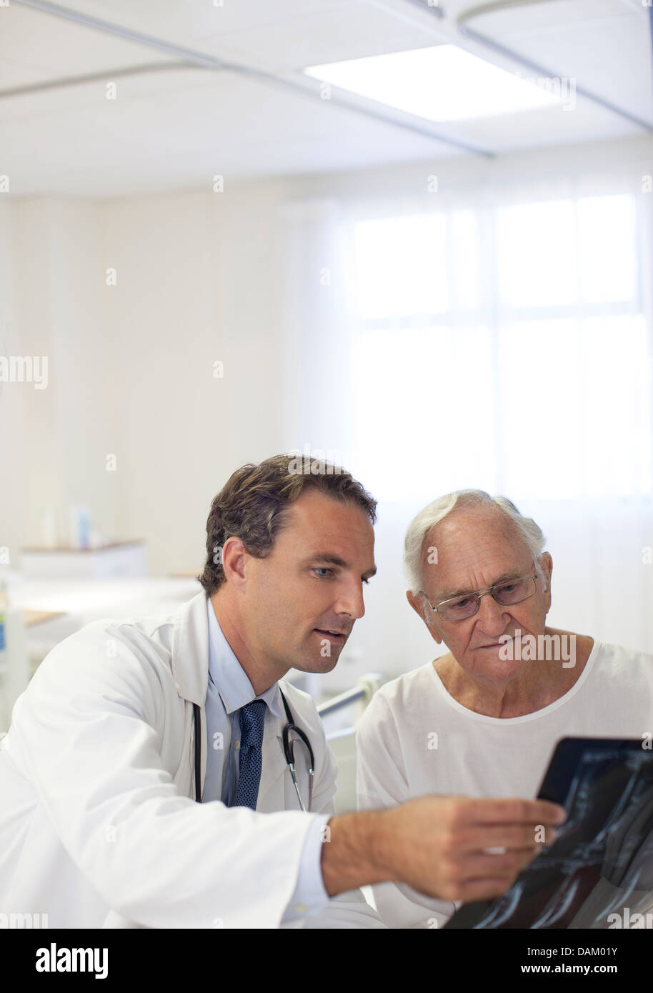 Doctor showing x-rays to older patient in hospital room - Stock Image