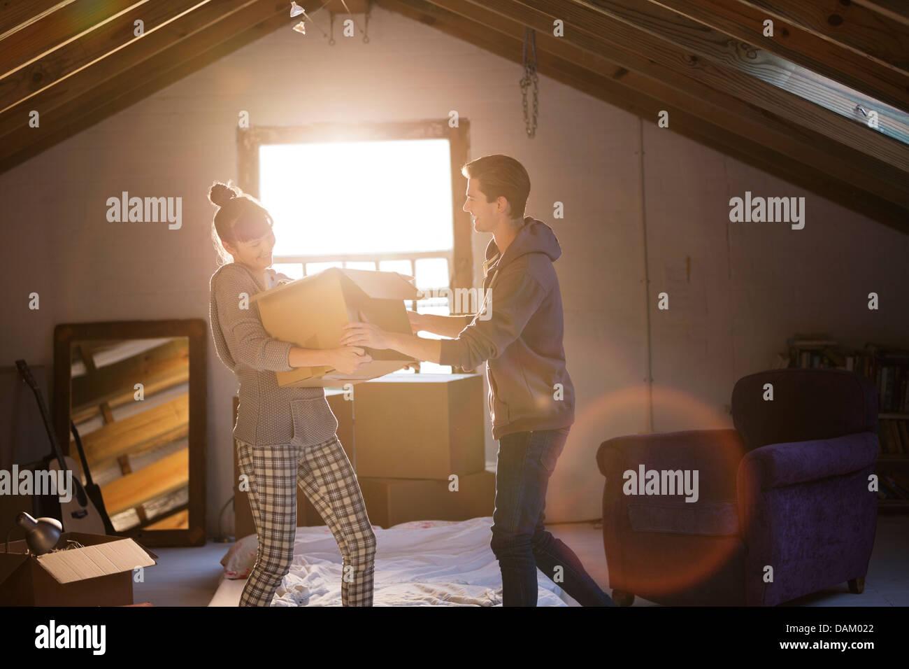 Couple unpacking box in attic - Stock Image