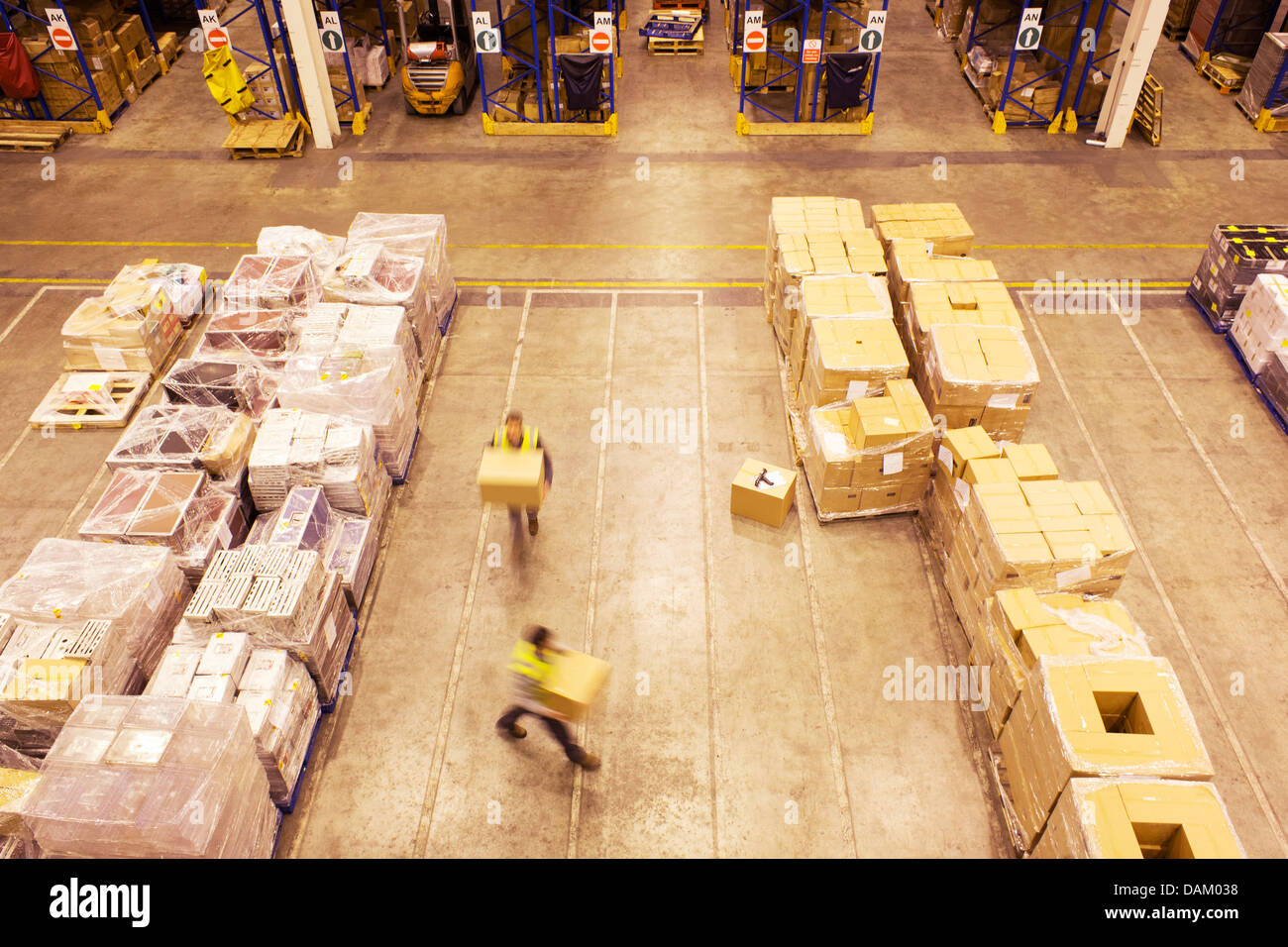 Blurred view of workers carrying boxes in warehouse - Stock Image