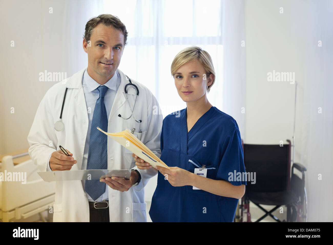 Doctor and nurse talking in hospital room - Stock Image
