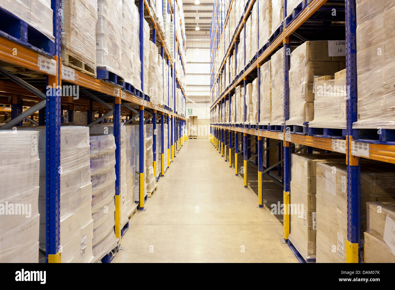 Stacks of boxes in aisle in warehouse - Stock Image
