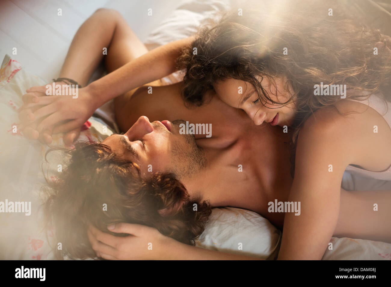 Couple relaxing together in bed - Stock Image