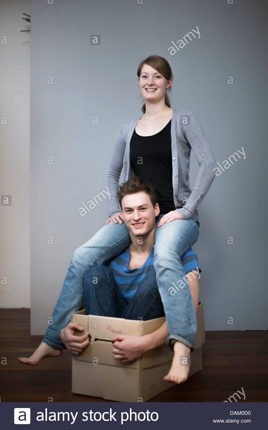 Young couple playing with a cardboard box - Stock Image