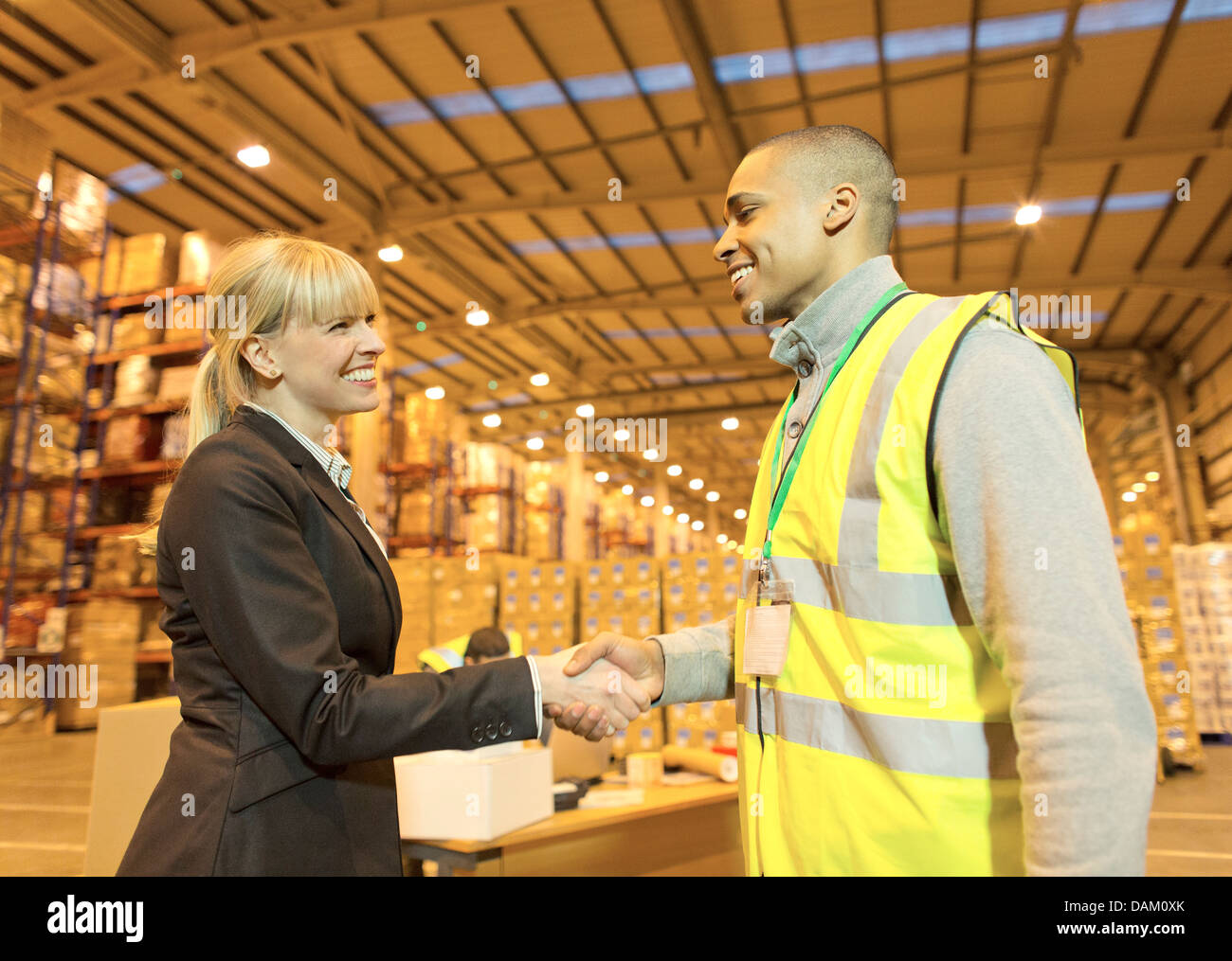 Businesswoman and worker shaking hands in warehouse - Stock Image