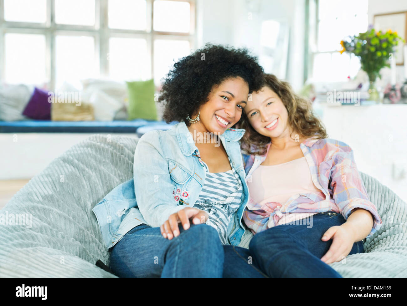 Women sitting in beanbag chair together - Stock Image