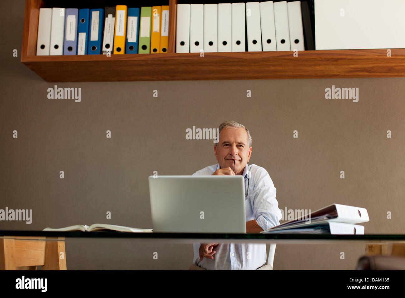 Older man sitting at desk - Stock Image