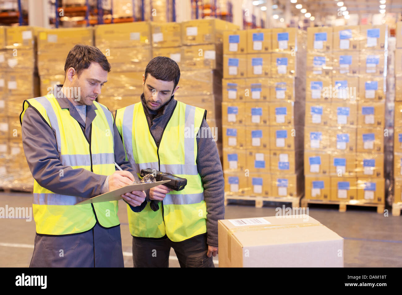 Workers writing on clipboard in warehouse - Stock Image