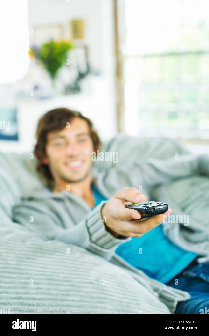Man watching television in beanbag chair - Stock Image