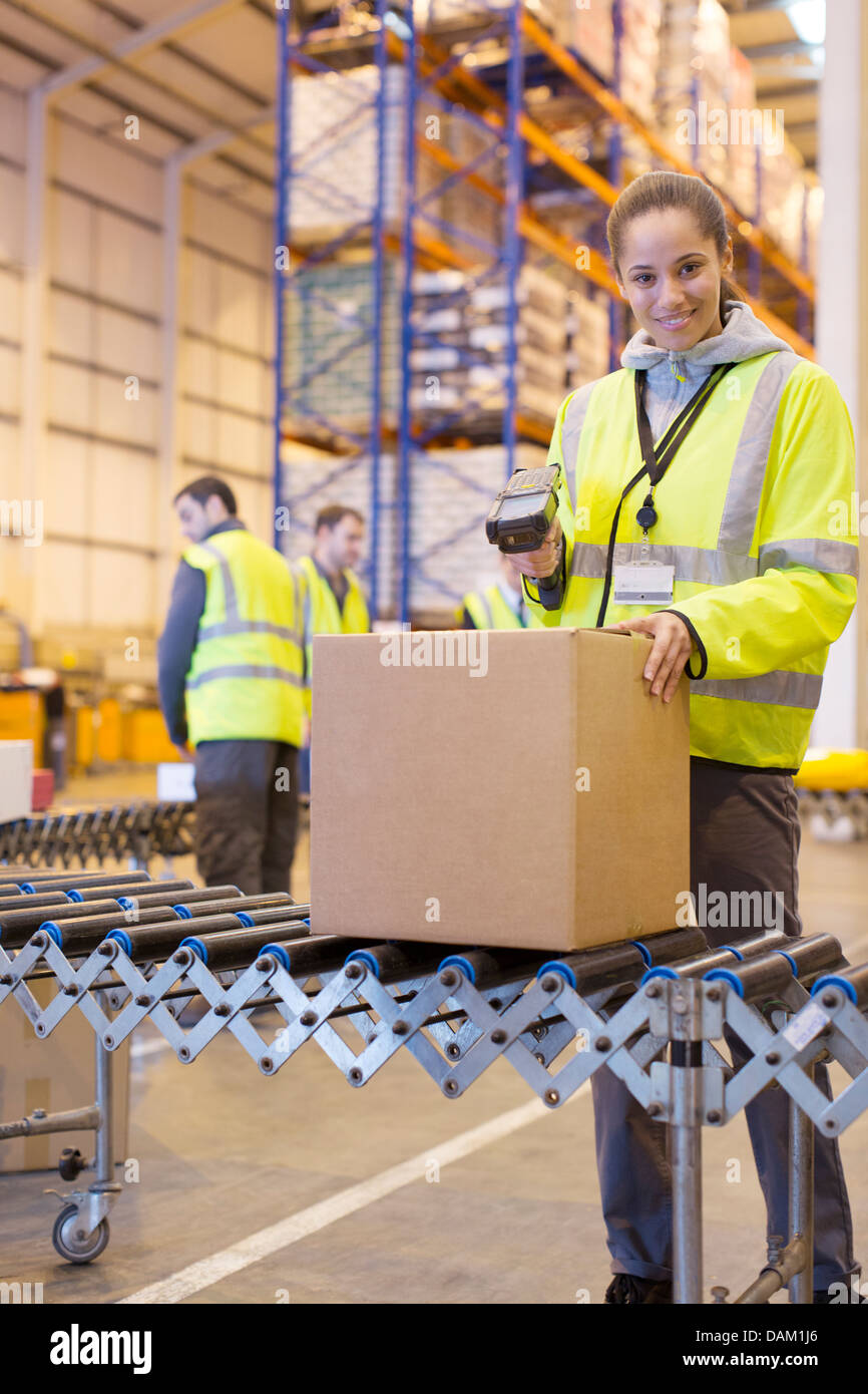 Worker scanning box on conveyor belt in warehouse - Stock Image