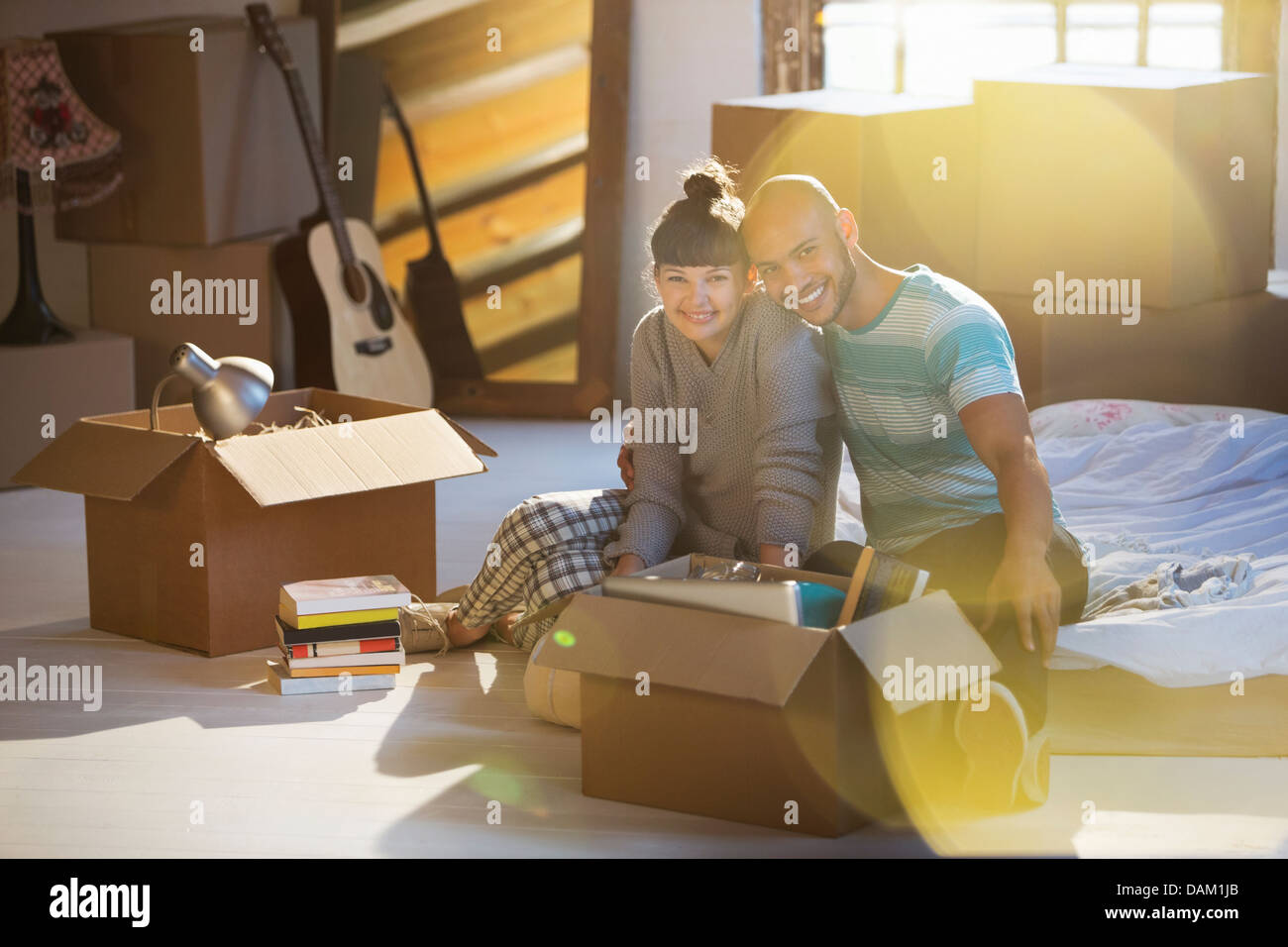 Couple unpacking boxes in attic - Stock Image
