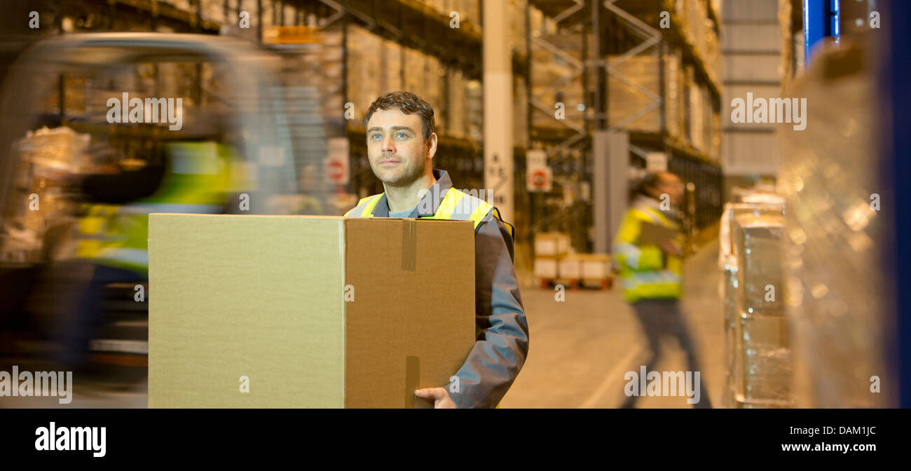 Worker carrying box in warehouse - Stock Image