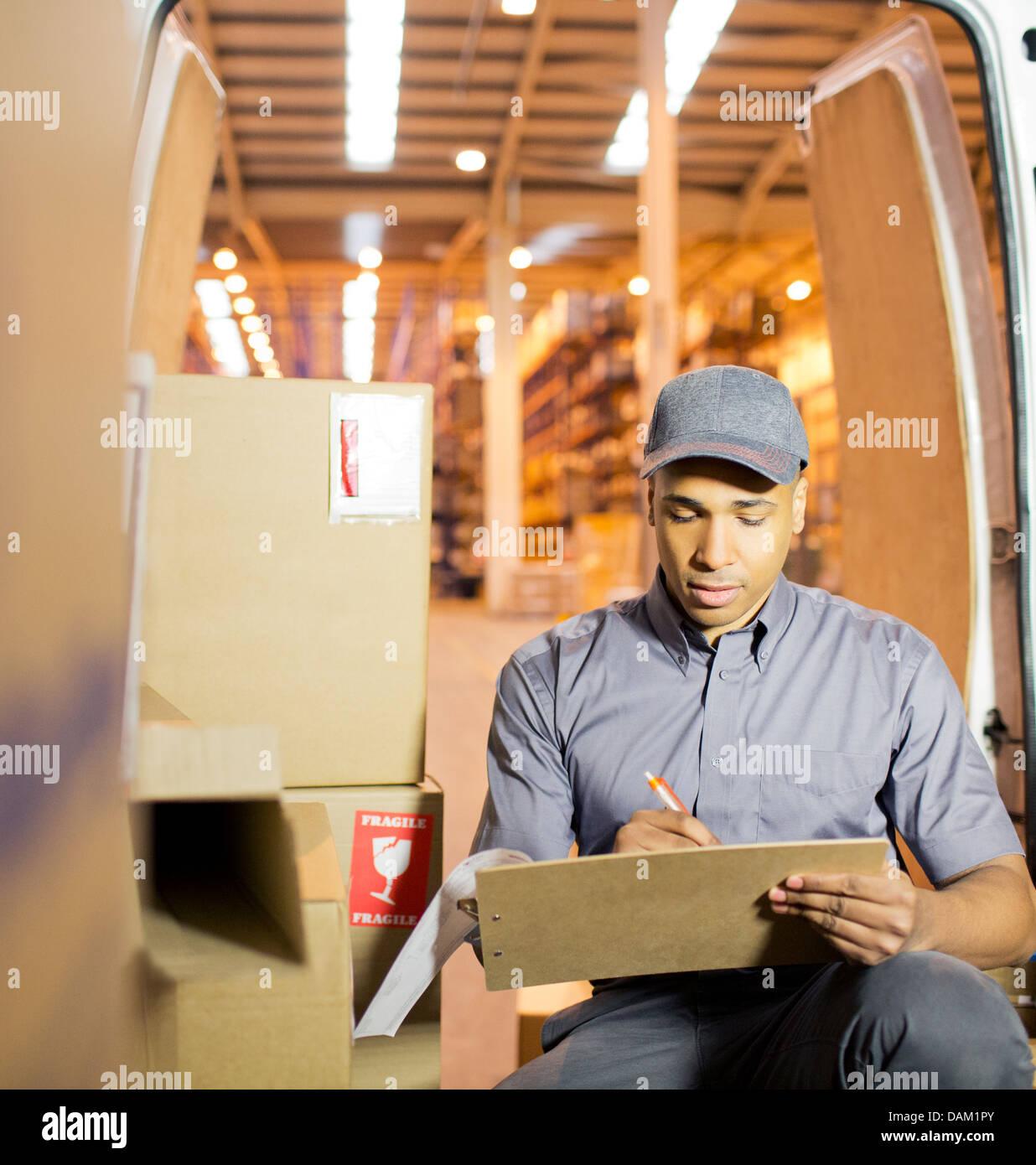 Delivery boy using clipboard in van - Stock Image