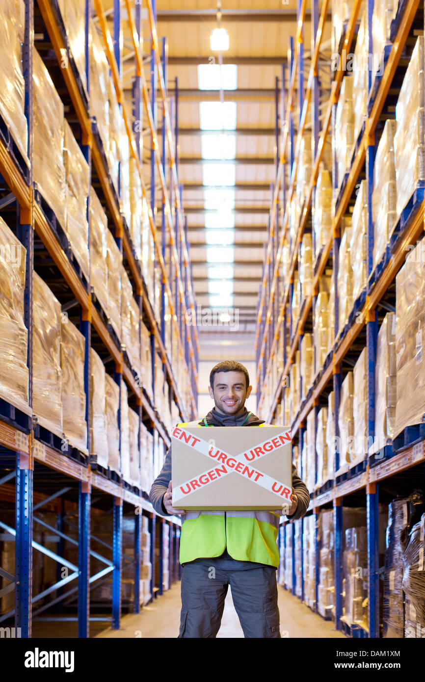 Worker carrying 'urgent' box in warehouse - Stock Image