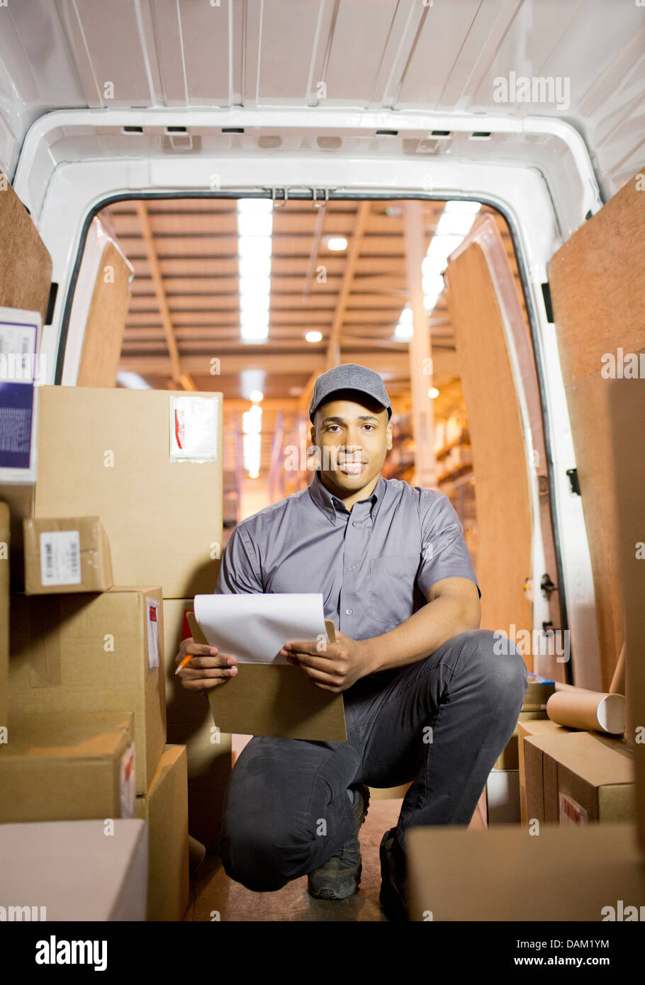 Delivery boy checking boxes in van - Stock Image