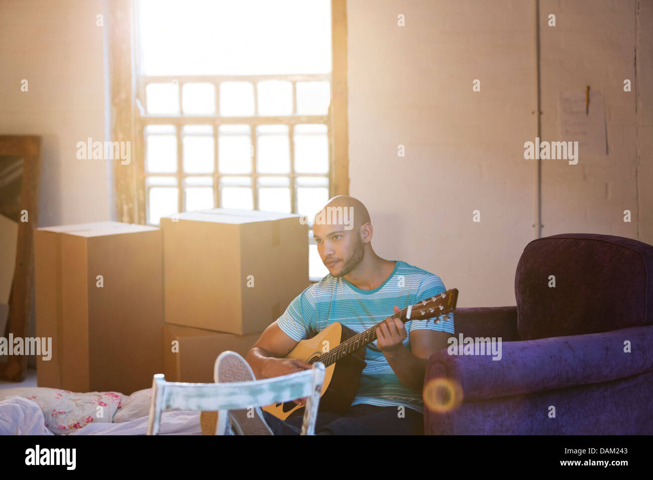 Man playing guitar in new home - Stock Image