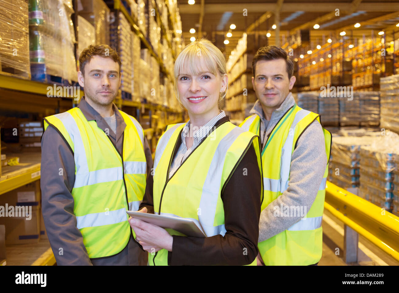 Businesswoman and workers smiling in warehouse Stock Photo