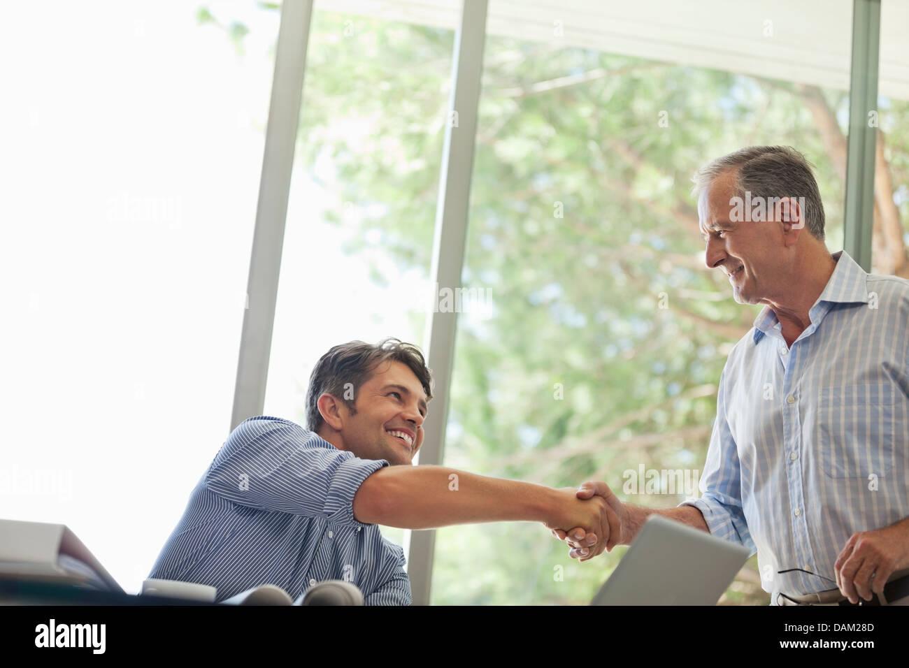 Men shaking hands in living room - Stock Image