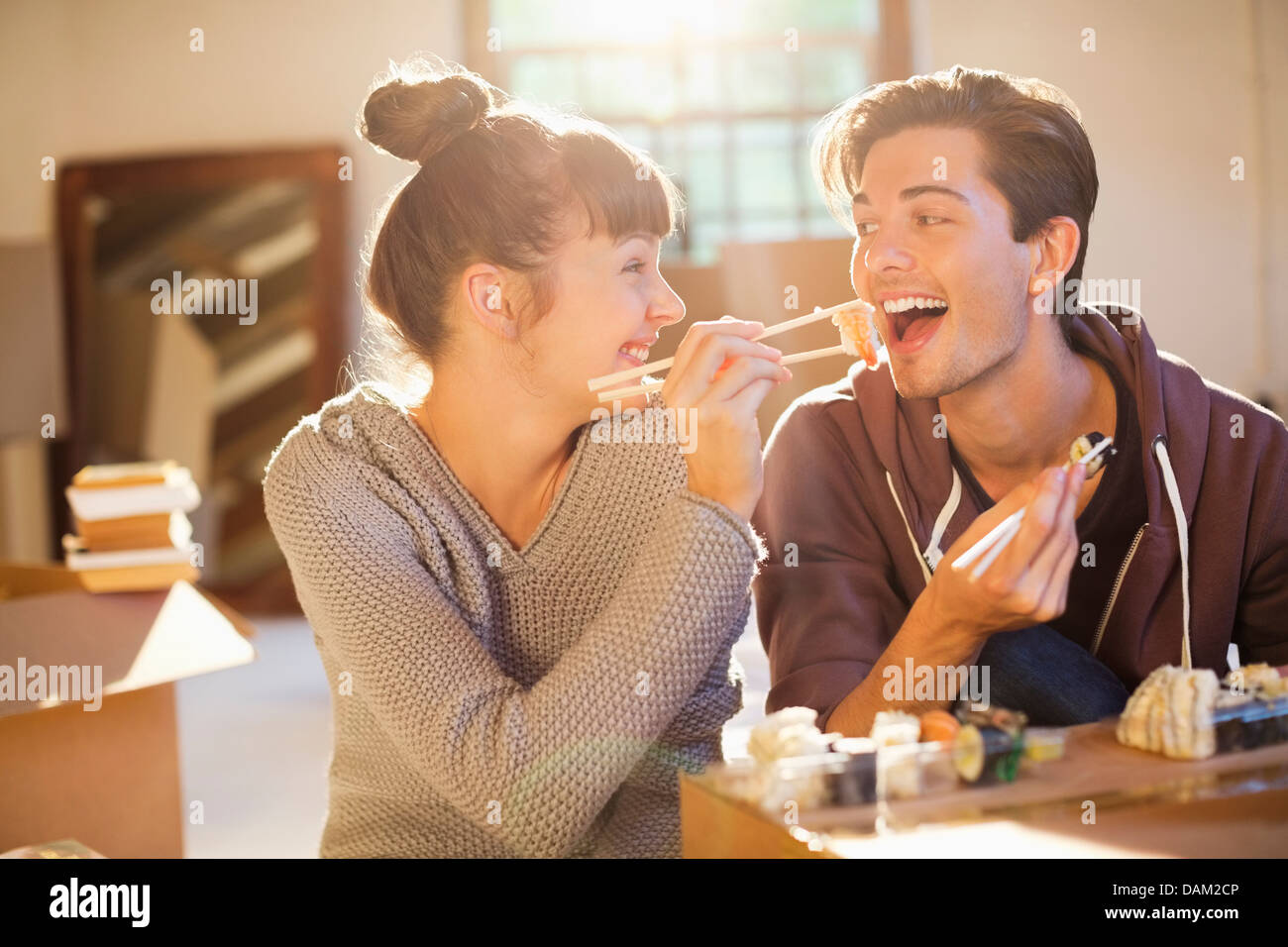 Couple eating sushi together in new home Stock Photo