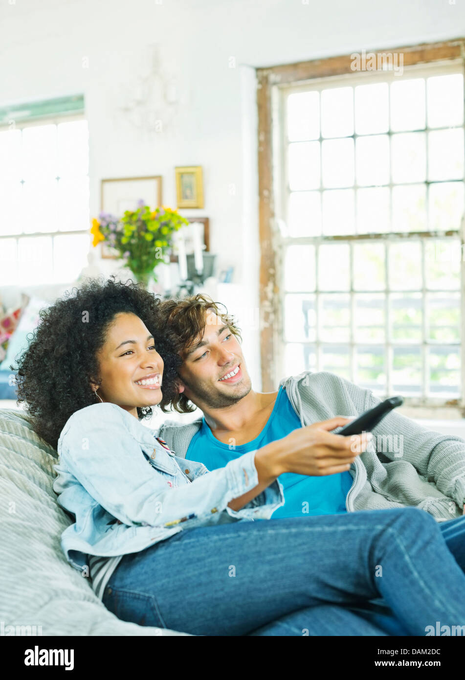 Couple watching television in beanbag chair - Stock Image