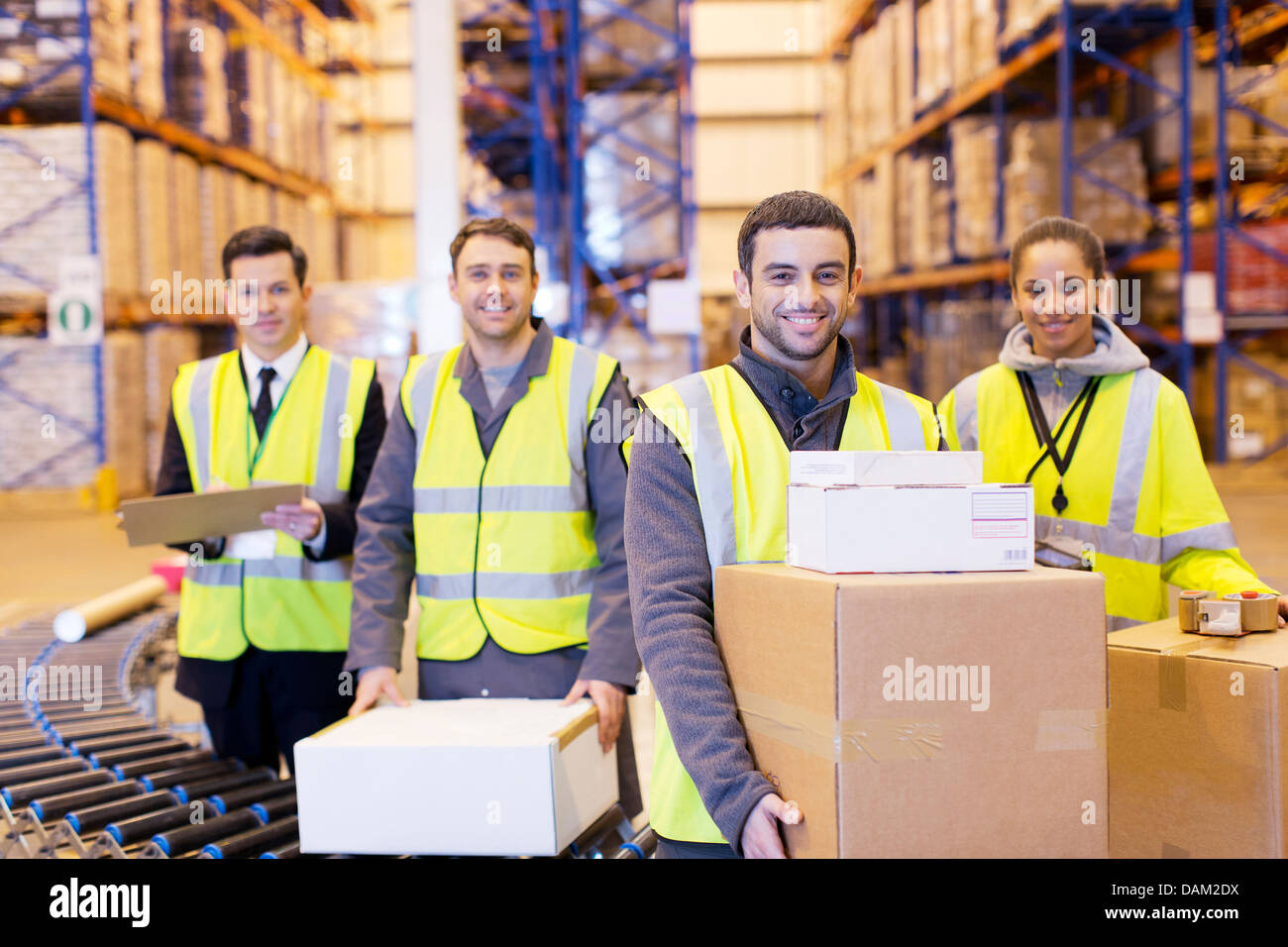 Workers smiling by conveyor belt in warehouse - Stock Image