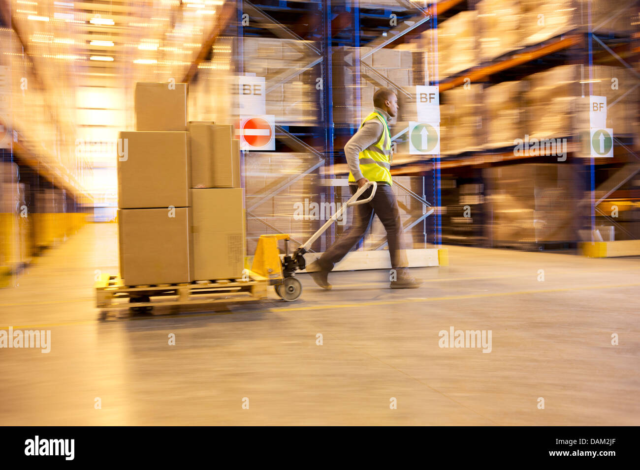 Blurred view of worker carting boxes in warehouse - Stock Image