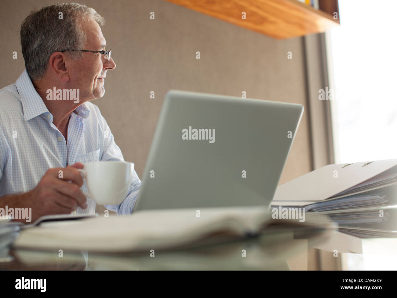 Businessman having cup of coffee at laptop - Stock Image