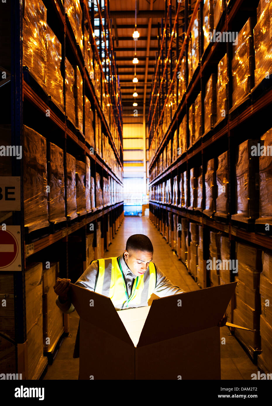 Worker opening glowing box in warehouse - Stock Image