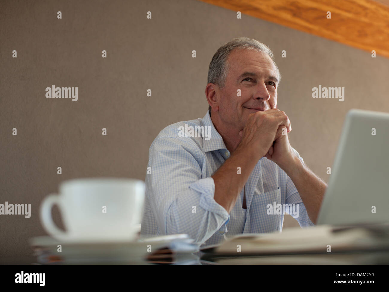 Businessman sitting at desk - Stock Image