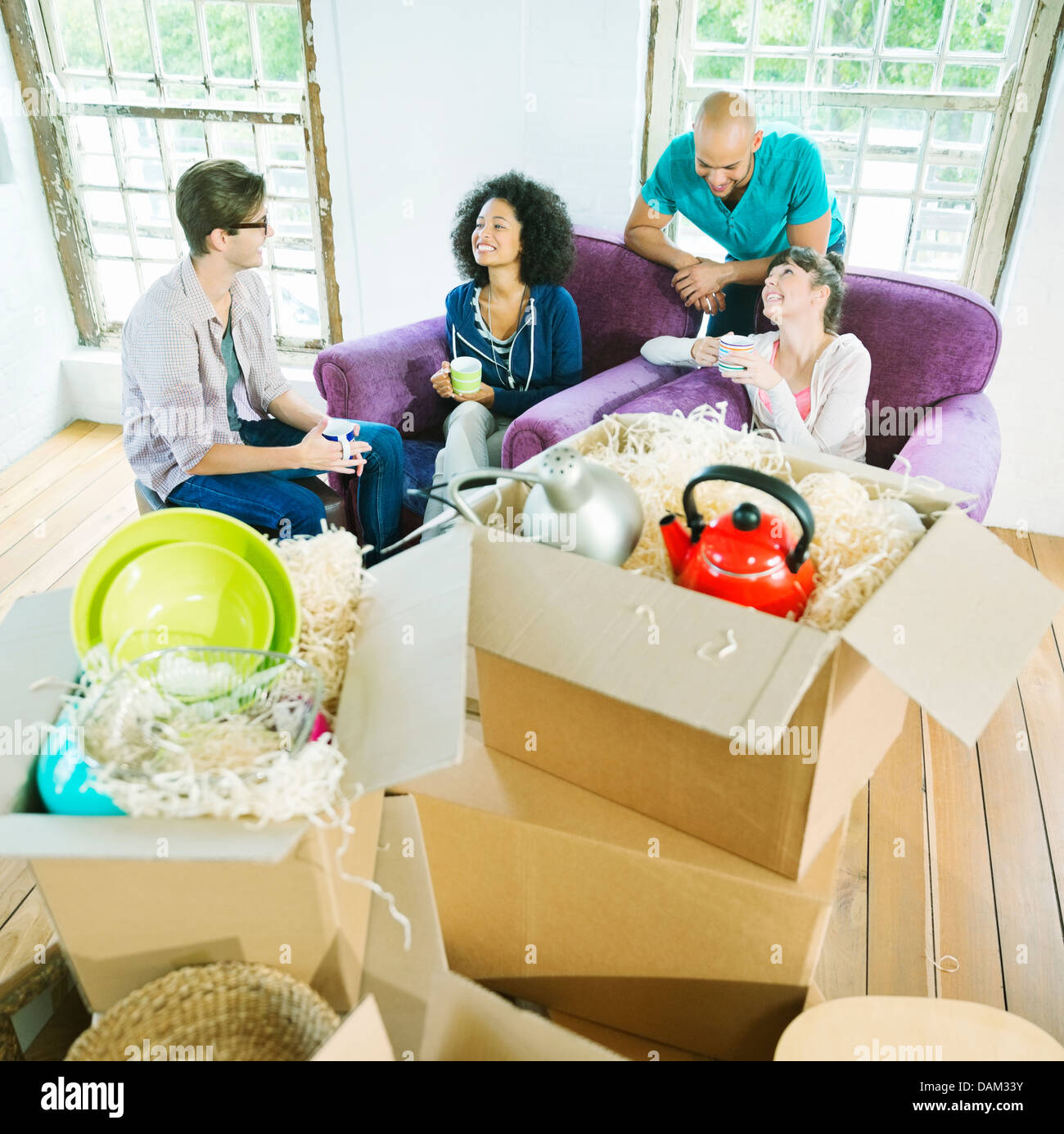 Friends relaxing in new home - Stock Image