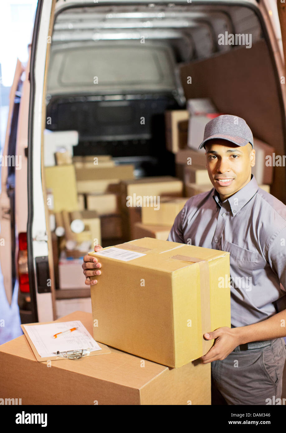 Delivery boy loading boxes into van - Stock Image