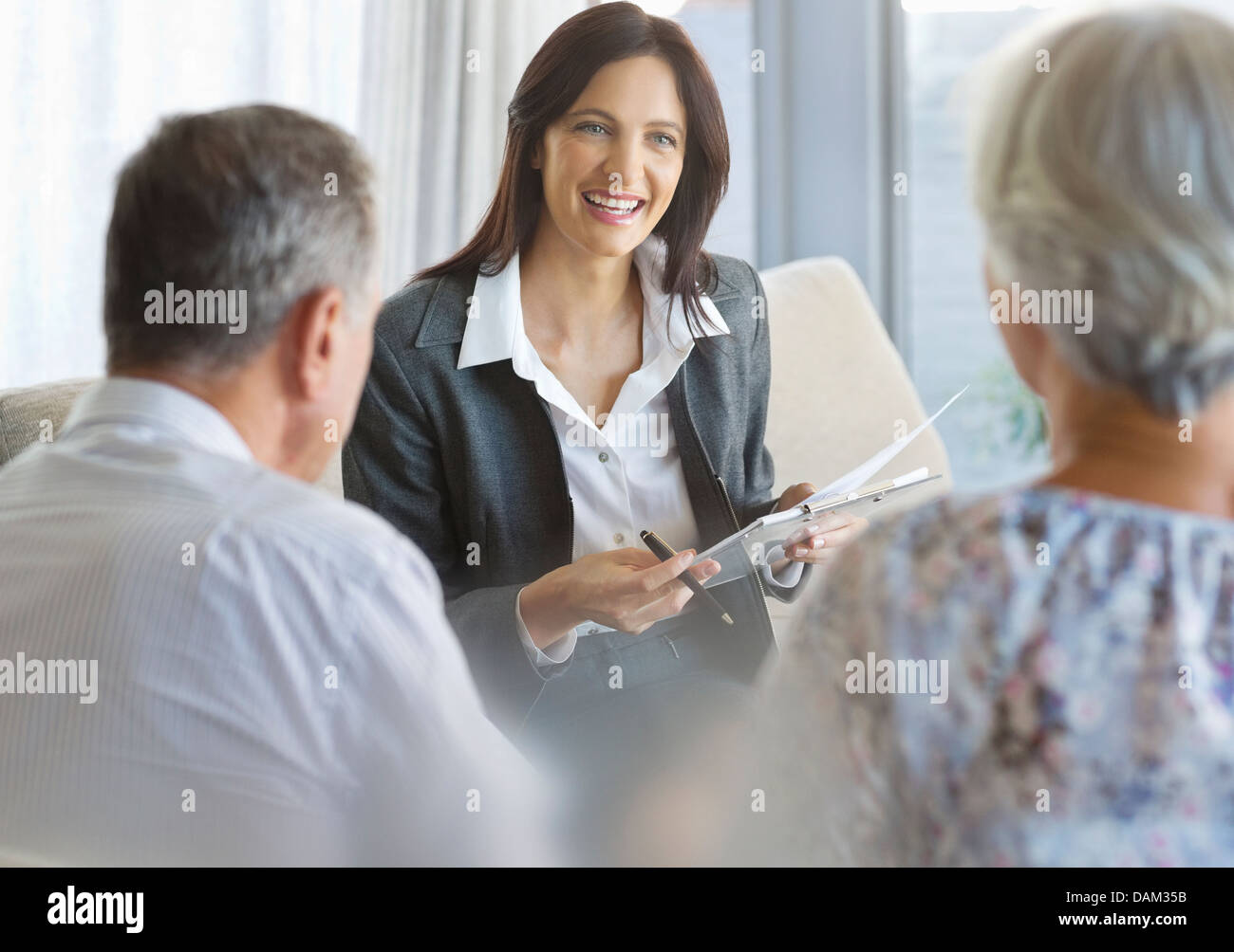 Financial advisor talking to clients in office - Stock Image