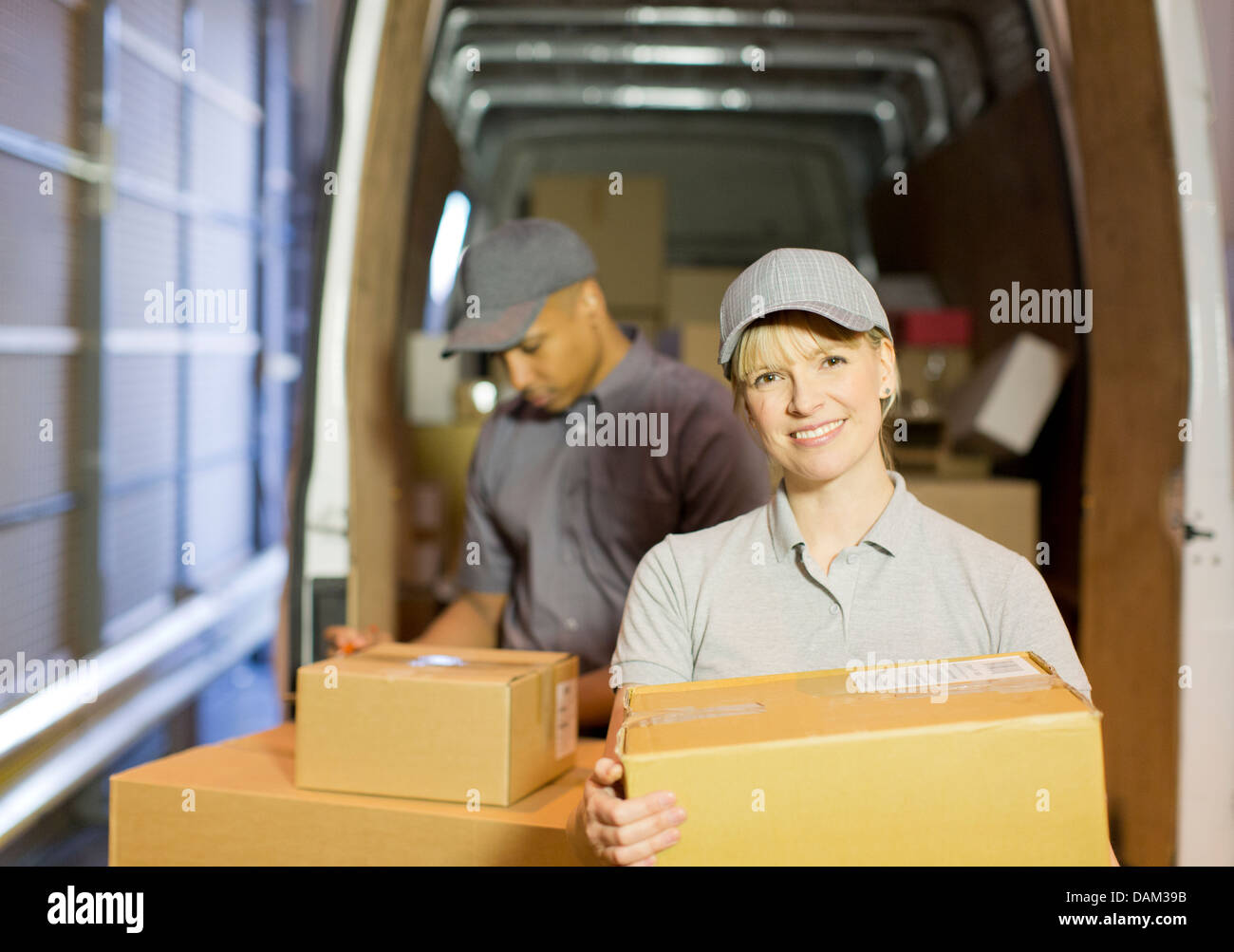 Delivery people loading boxes into van - Stock Image