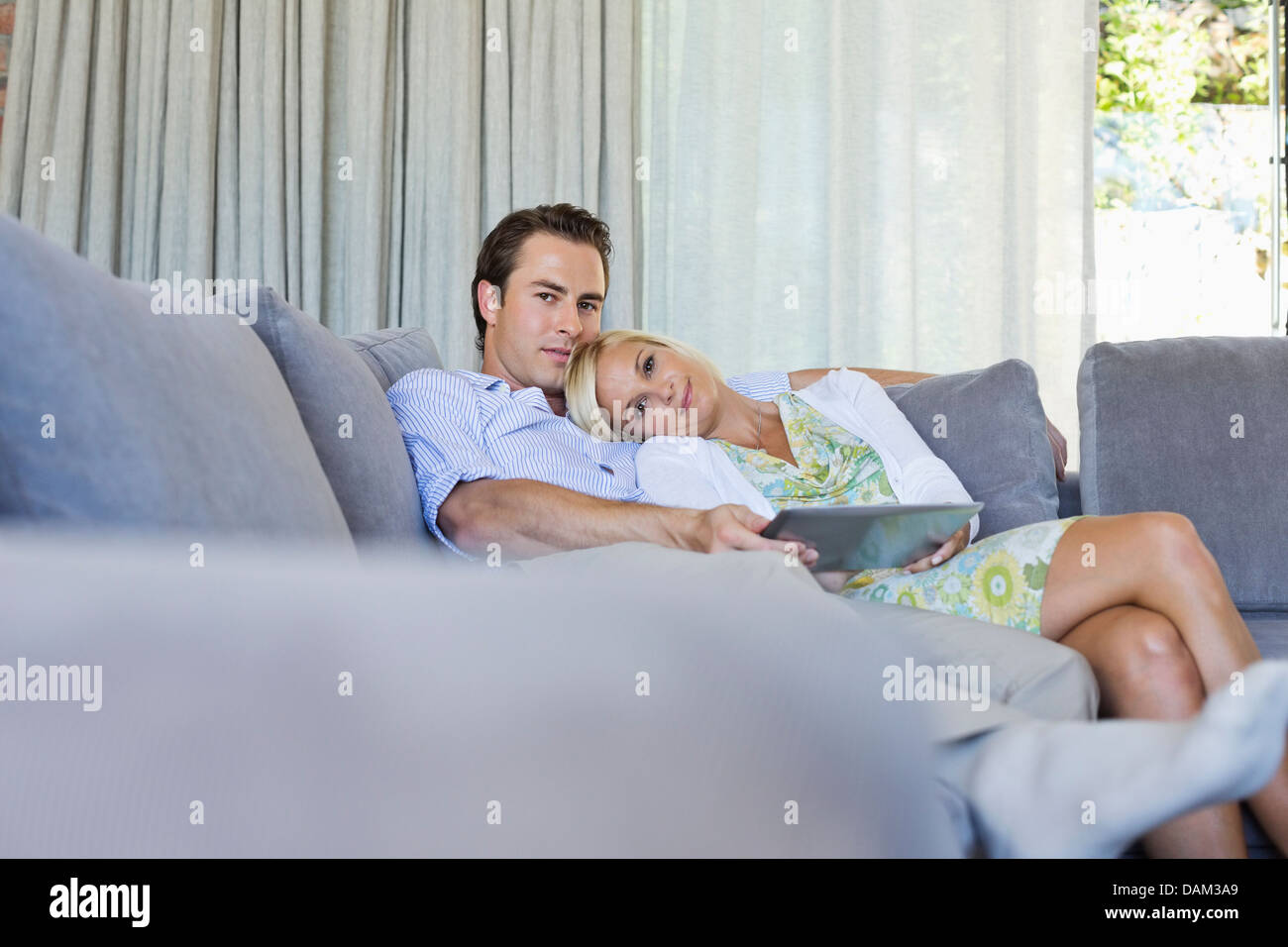 Couple relaxing on sofa together - Stock Image