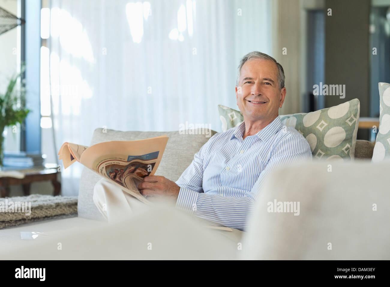 Older man reading newspaper on sofa - Stock Image