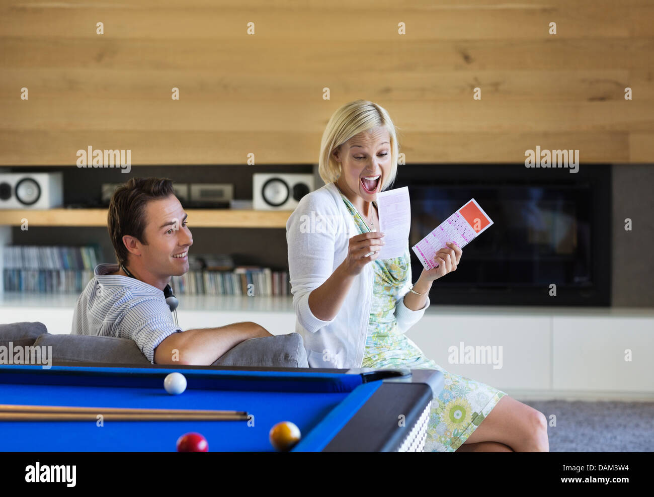 Couple checking lottery tickets on sofa - Stock Image