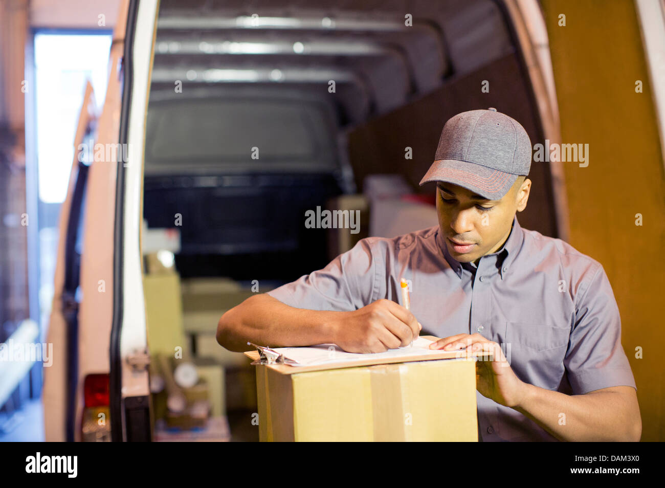 Delivery boy writing on clipboard in van - Stock Image