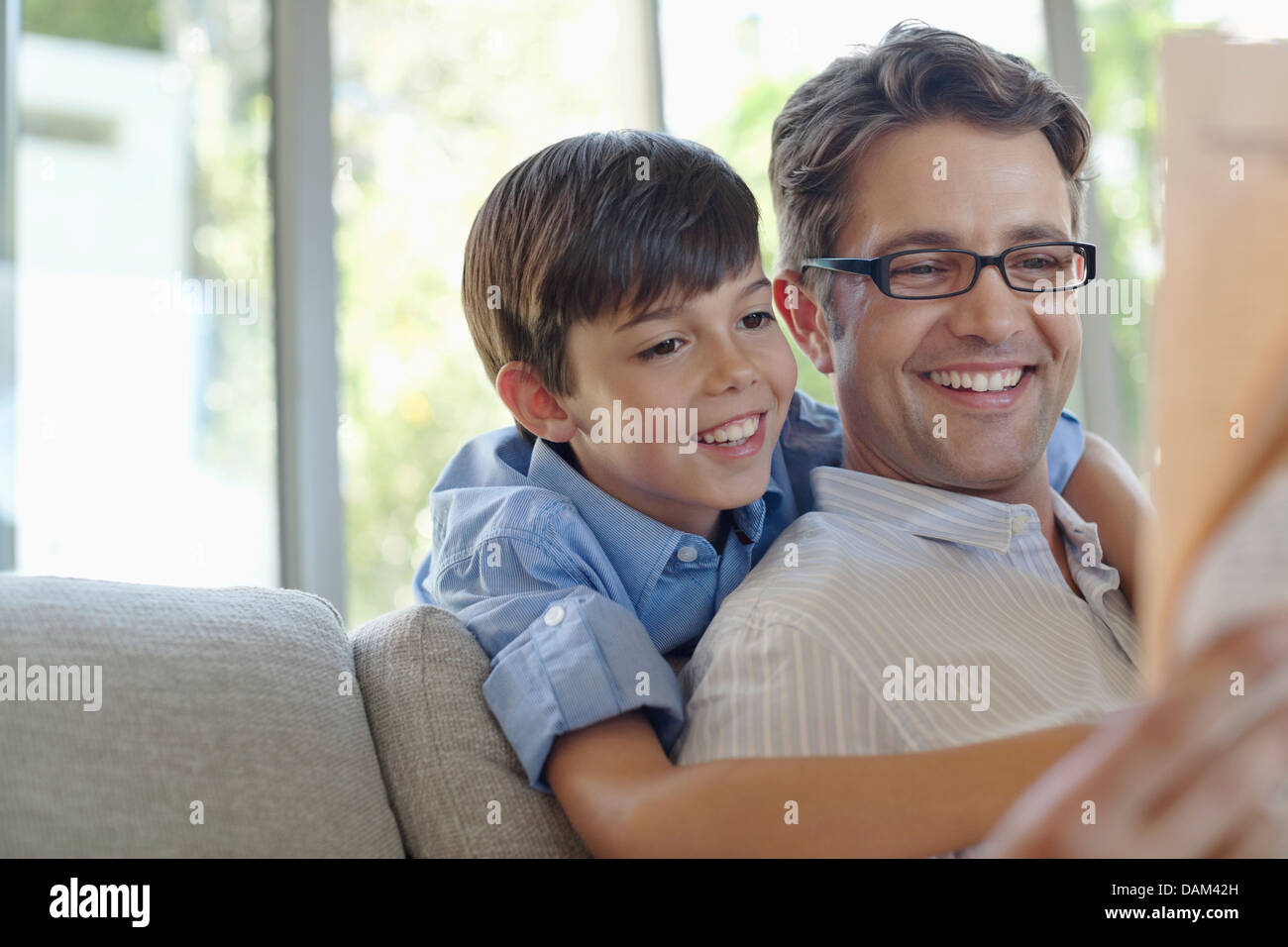 Father and son hugging on sofa - Stock Image