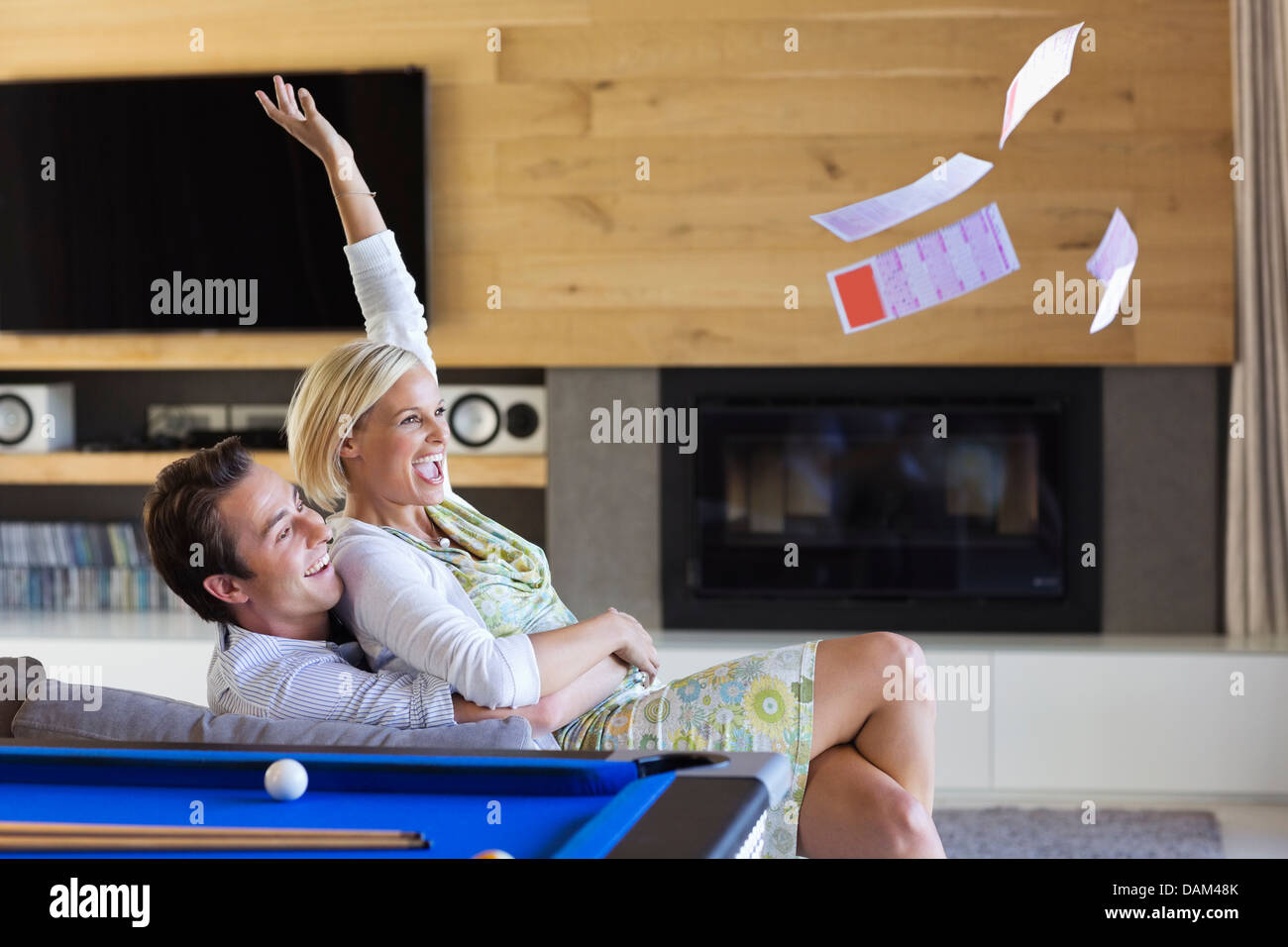 Woman tossing lottery tickets in living room Stock Photo