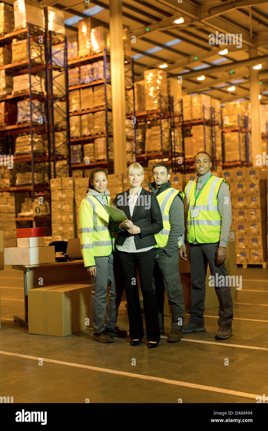 Businesswoman and workers smiling in warehouse - Stock Image