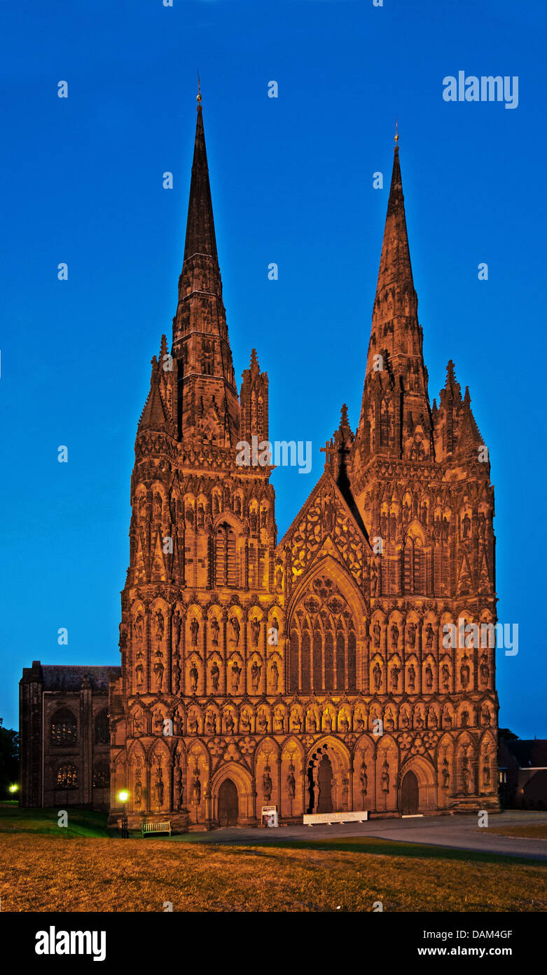 Flood lit west front of Lichfield Cathedral of St Chad with blue of late evening sky - Stock Image
