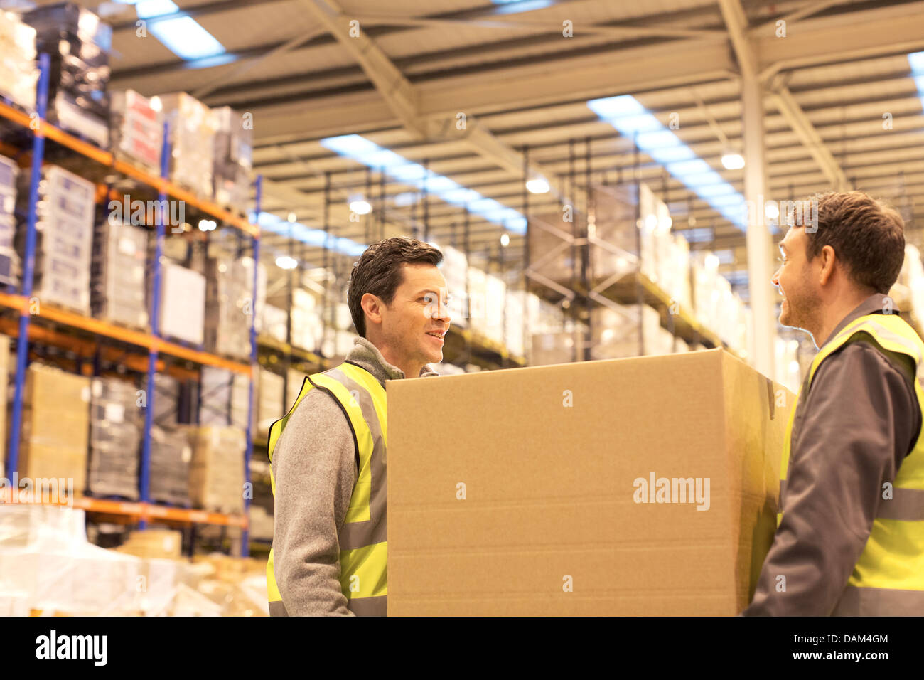 Workers carrying box in warehouse - Stock Image